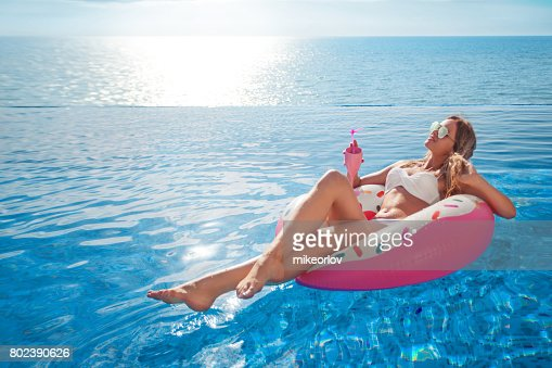 Summer Vacation. Woman in bikini on the inflatable mattress in the SPA swimming pool. : Stock Photo