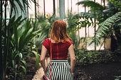 Young pretty woman walking in botanical garden, enjoying the nature