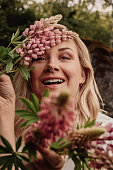 Summer woman portrait with flowers outdoors in nature Close up of female in summer dress holding flowers