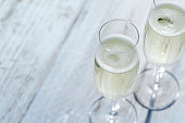 Two glasses of Prosecco or Champagne on a garden picnic table outdoors in Springtime or Summertime.