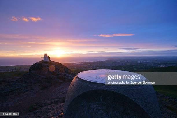 Summit trigpoint vista in summer dawn sunlight