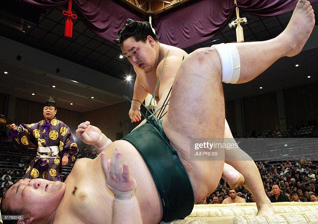 Sumo grand champion Asashoryu throws Iwakiyama to the ground during the third day bout of the 15day long Kyushu Grand Sumo Tournament in Fukuoka...