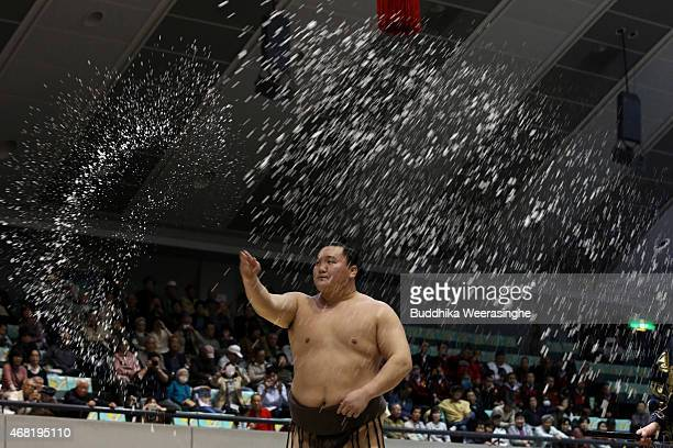 Sumo Grand Champion Hakuho Sho throws salt before competing in the Grand Sumo Tournament at the Himeji Chuo Gymnasium on March 31 2015 in Himeji...