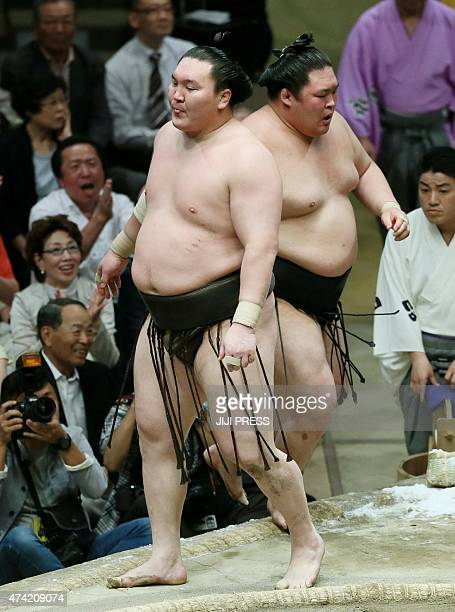 Sumo grand champion Hakuho sticks out his tongue after he was thrown by champion Goeido at the 12th day bout of the Summer Grand Sumo Tournament in...