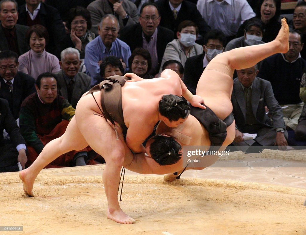Sumo grand champion Hakuho throws Asashoryu to win during the final day of Grand Sumo Kyushu Tournament on November 29 2009 in Fukuoka Japan