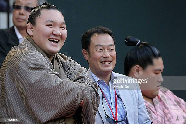 Sumo Grand Champion Hakuho whose real name is Munkhbat Davaajargal smiles as he watches the match between Gael Monfils of France and Andreas Seppi of...