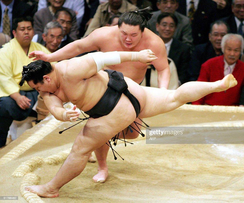 Sumo grand champion or 'yokozuna' Asashoryu steps out of the ring while maegashiraranked wrestler Hakuho pushes him from the behind during their...