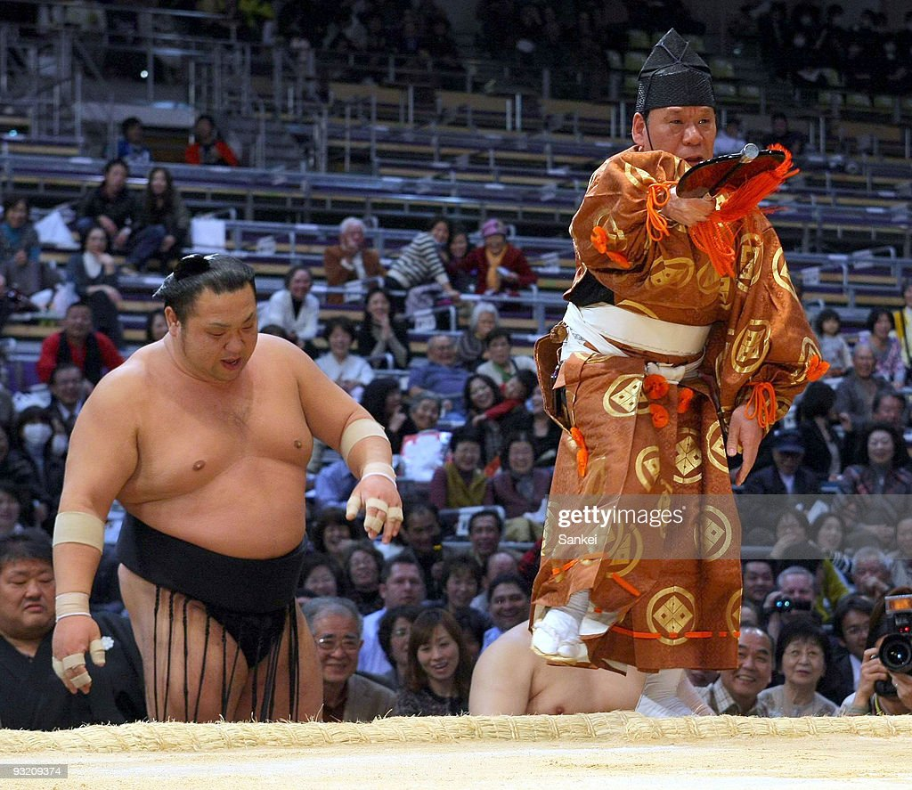 Sumo referee Tamamitsu Kimura announces the win to Goeido after being thrown out from the ring during the day four of Grand Sumo Kyushu Tournament at...