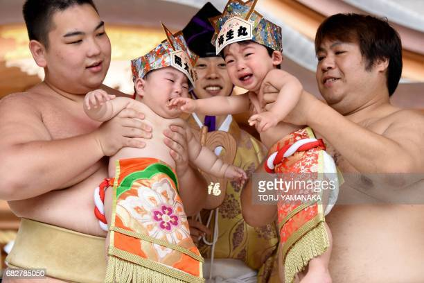 Sumo wresters hold up crying babies in front of a referee clad in a traditional costume during a 'Babycry Sumo' event at the KamegaikeHachiman Shrine...