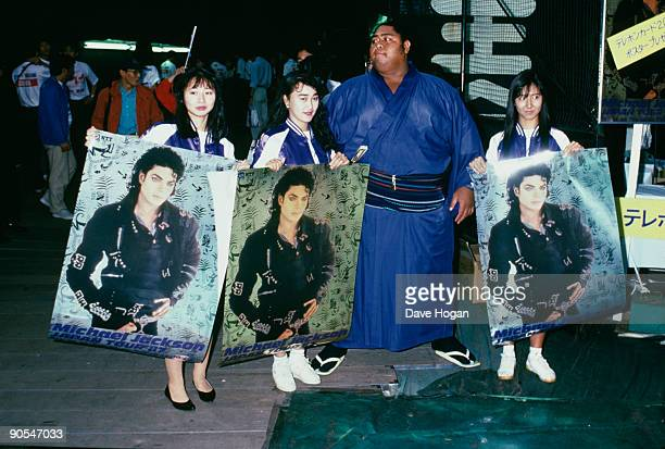 Sumo wrestler Konishiki and Japanese fans of Michael Jackson holding tour poster portraits of the singer outside a concert venue in Japan September...