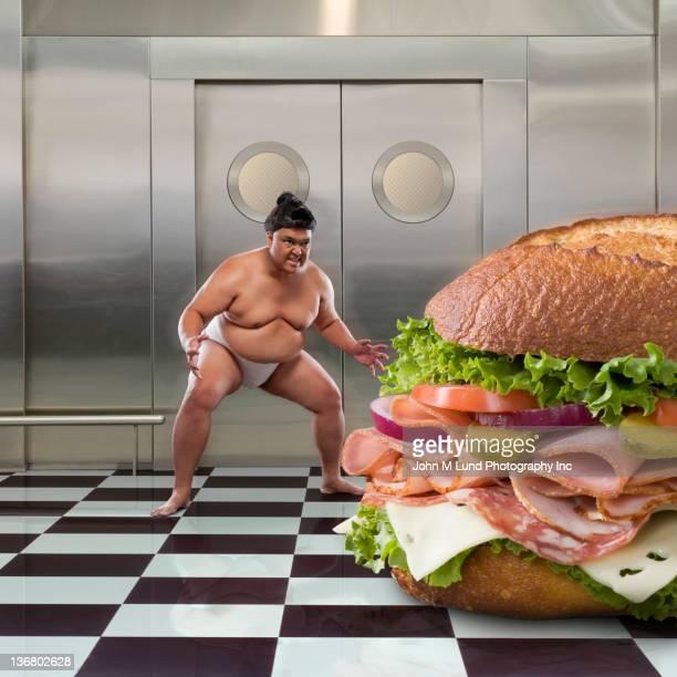 Sumo wrestler next to large sandwich
