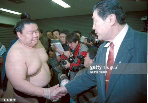 Sumo wrestler Takatoriki shakes hands with his stable master Taiho after winning the Grand Sumo Spring Tournament on March 26 2000 in Osaka Japan...