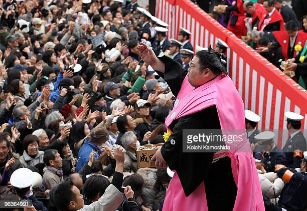 Sumo Wrestler Yamamotoyama throws packs of beans during a beanscattering ceremony at Shinshoji Temple on February 3 2010 in Narita Japan The ceremony...