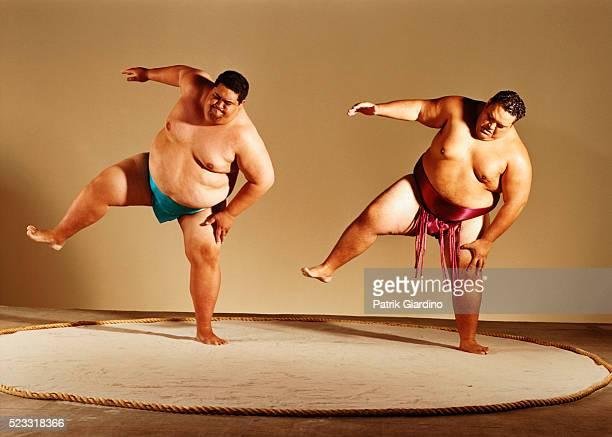 Sumo Wrestlers Lifting Legs