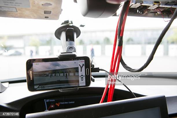 A Sumsung Electronics Co smartphone camera displays a wrongway driver warning app as it sits on the windshield of a Bayerische Motoren Werke AG 3...