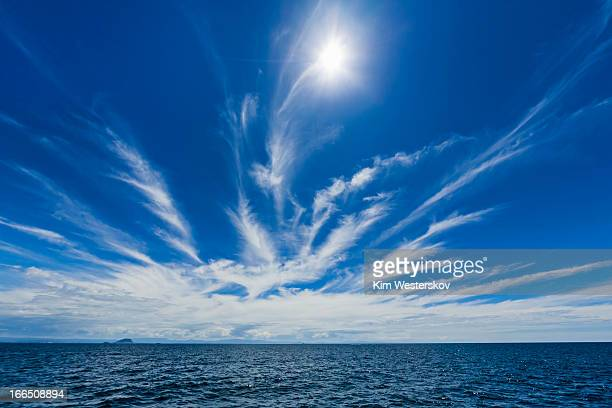 Sun and cirrus clouds over sea
