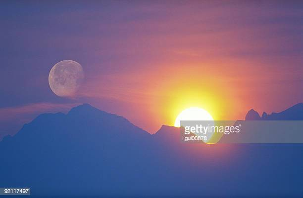 sun and moon behind mountain