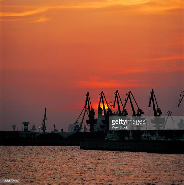 sun and silhouette of cranes at harbour,Qinhuangdao,Hebei,China
