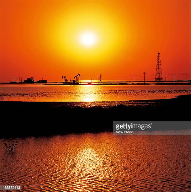 sun and silhouette of oil extraction equipment on sea,Shandong,China