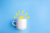 sun and white cup on blue background. good morning concept
