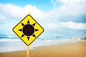 Sun on a yellow warning sign with wooden post at the beach