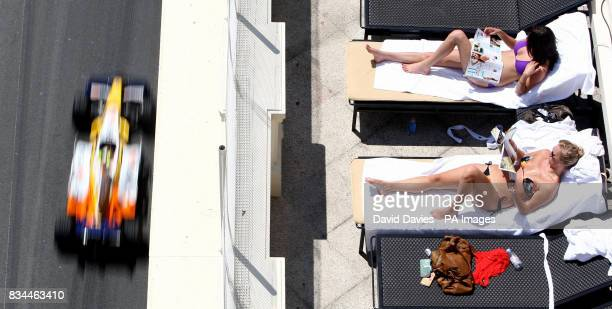 Sun bathers enjoy the weather as Fernando Alonso drives his Renault during the practice session at Monte Carlo Monaco