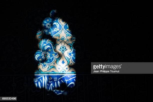 Sun beams illuminating the arabesque pattern on the tiles of Sheikh Lotfollah Mosque, Isfahan, Iran