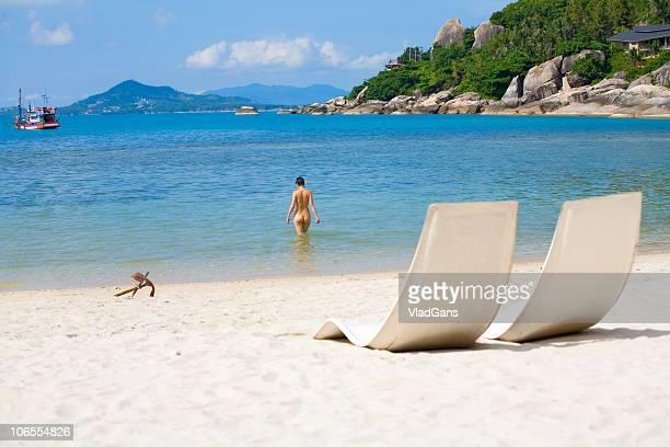 Sonnenliegen und Mädchen im Meer und Strand