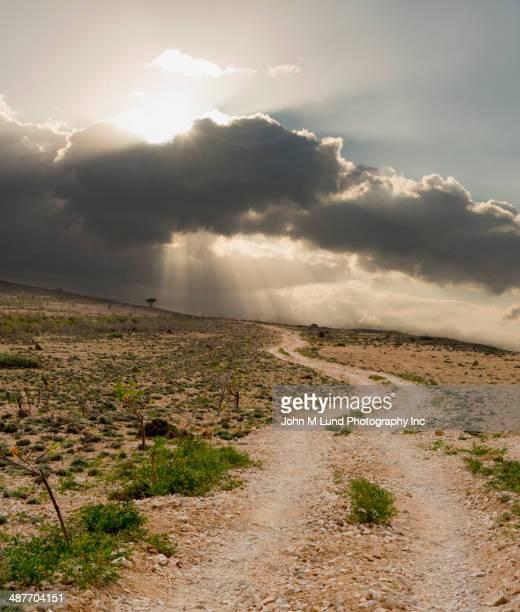 Sun breaking through clouds over arid landscape