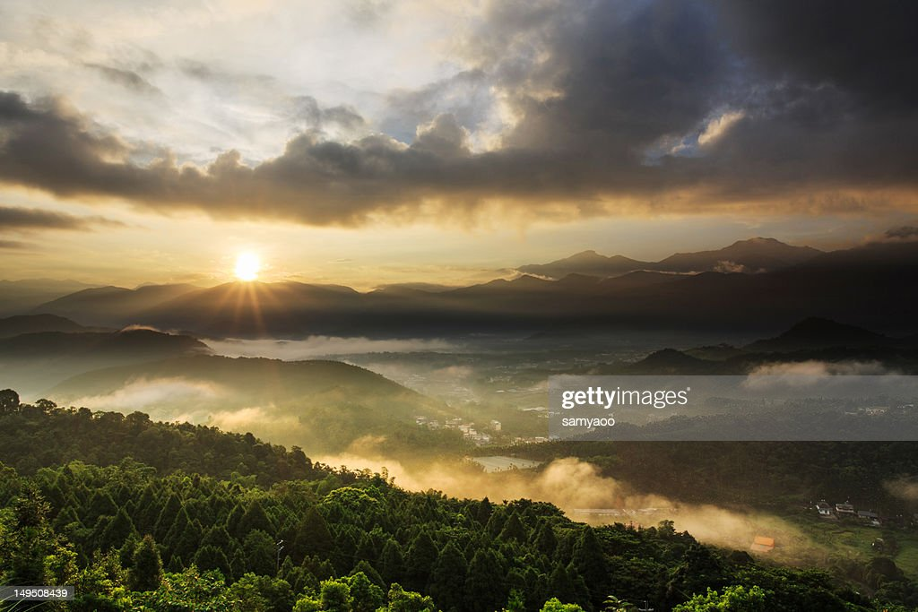 Sun burst in misty valley : Stock Photo