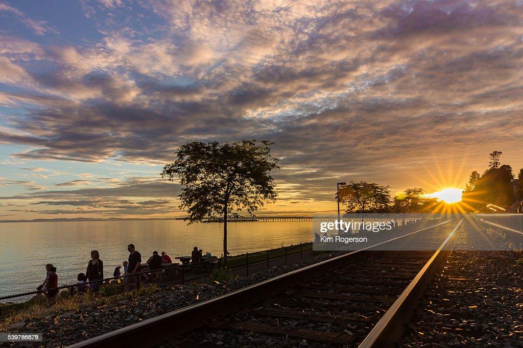 Sun burst lights up the train tracks of White Rock, BC, Canada