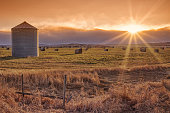 Landscape of the setting sun on the prairie with a grain elevator and sunburst.