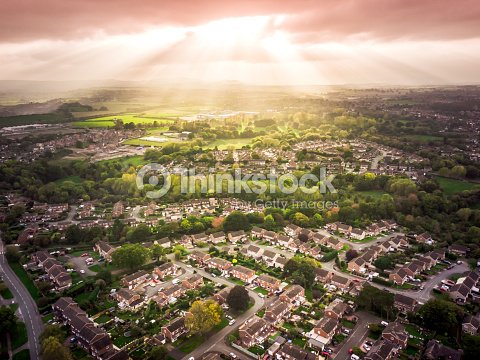 Sun bursting through clouds over traditional British houses with countryside in the background. : Foto de stock