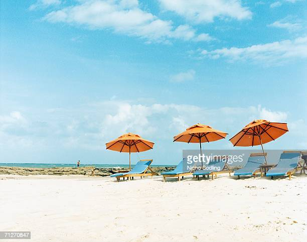 Sun chairs and parasols on a beach.