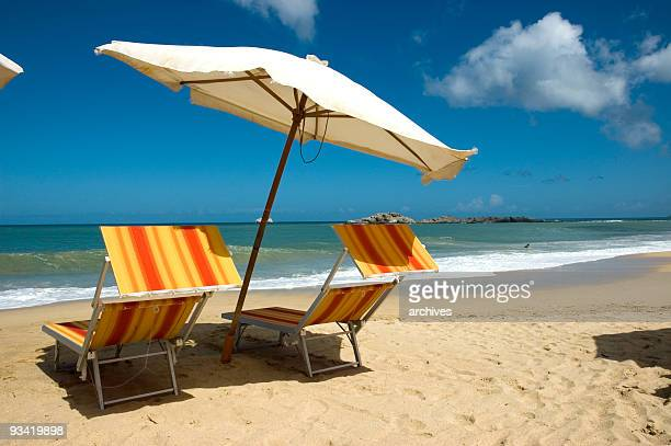sun chairs with white umbrella