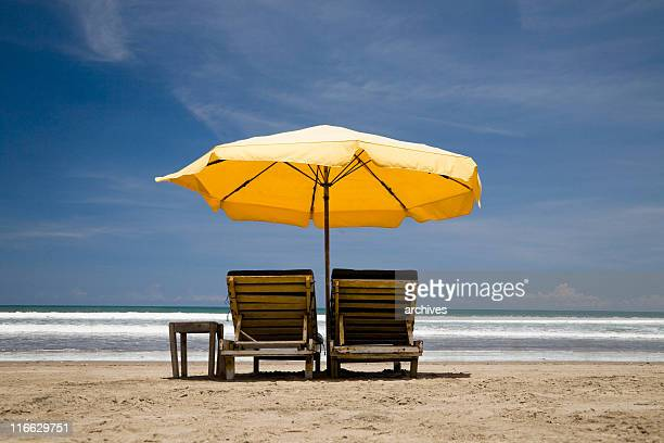 sun chairs with yellow umbrella