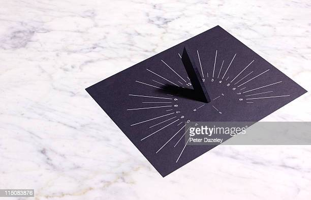 Sun dial on marble background
