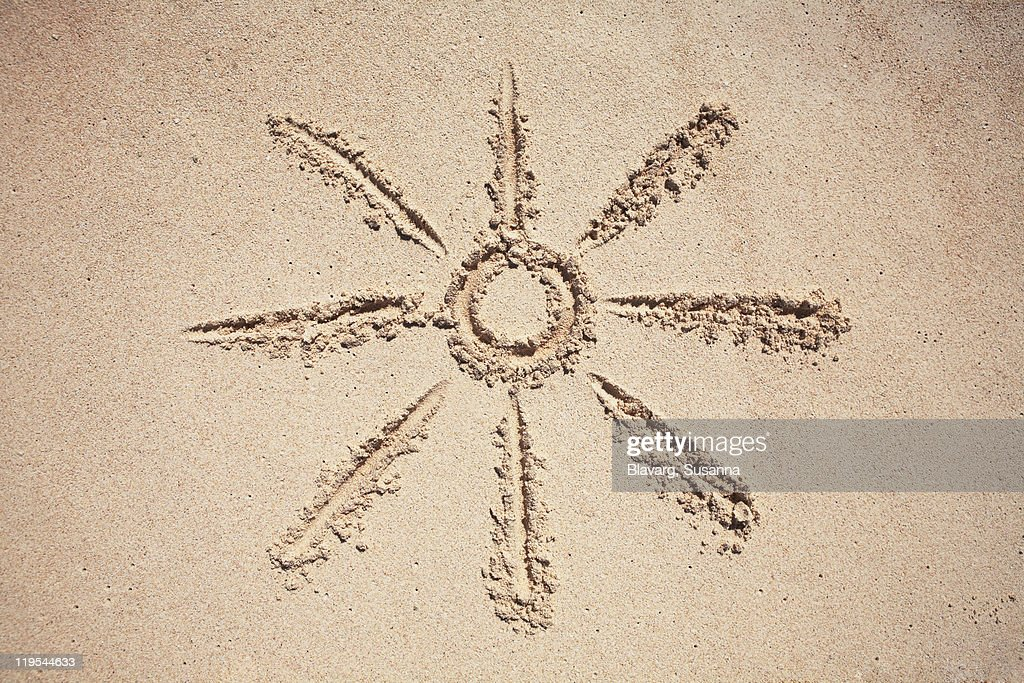 Sun drawing on sand : Stock Photo
