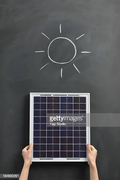 Sun drawing on the blackboard with solar panel