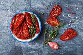Sun dried tomatoes with thyme in a bowl on stone black table top view. Natural antipasto, appetizer or refreshment.