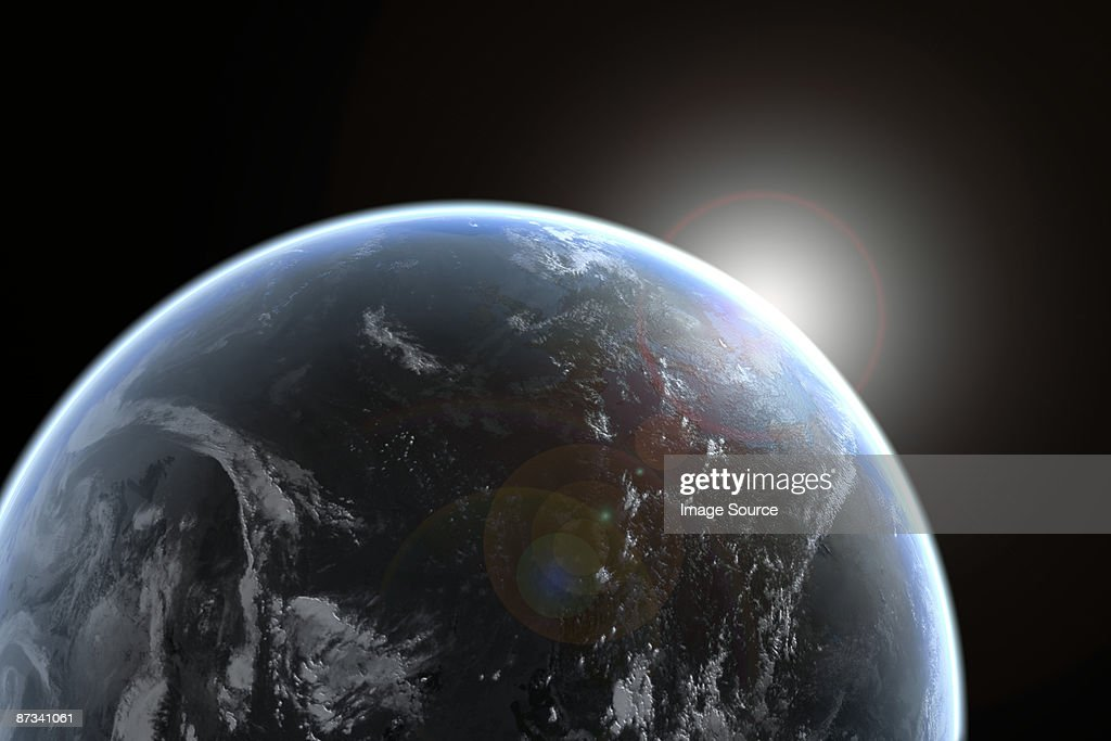 Sun emerging over planet earth : Stock Photo