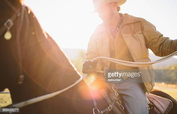 Sun glares as man holds back reins while riding horseback