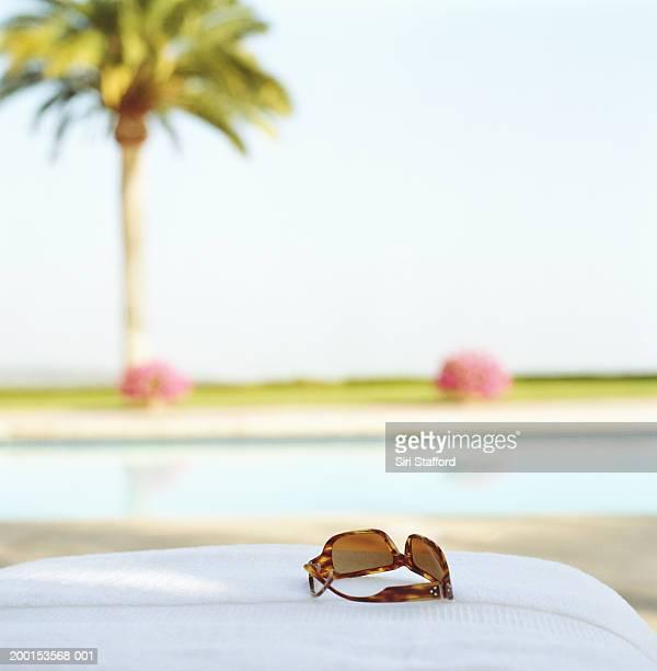 Sun glasses sitting near pool