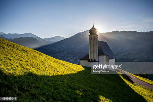 A sun goes down behind the chapel in Zillertal region on October 23 2015 in Hartberg Austria The Zillertal area located in central Tyrol is a popular...