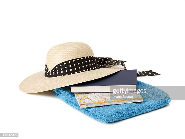 Sun hat beach towel book and map