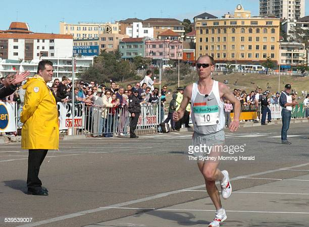 Sun Herald City to Surf Third place runner Steve Moneghetti reaches the finish line at Bondi 8 August 2004 SMH Picture by JANIE BARRETT
