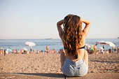 Beautiful brunette girl holding her hair up and sitting on the sandy beach