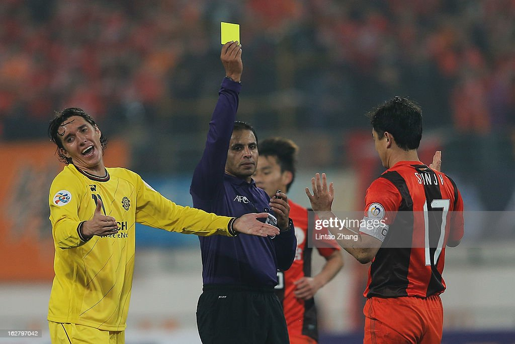 Sun Jihai (R) of Guizhou Renhe is shown a yellow card by Referee Khalil Al Ghamdi (C) with Cleo of Kashiwa Reysol during the AFC Champions League match between Guizhou Renhe and Kashiwa Reysol at Olympic Sports Center on February 27, 2013 in Guiyang, China.