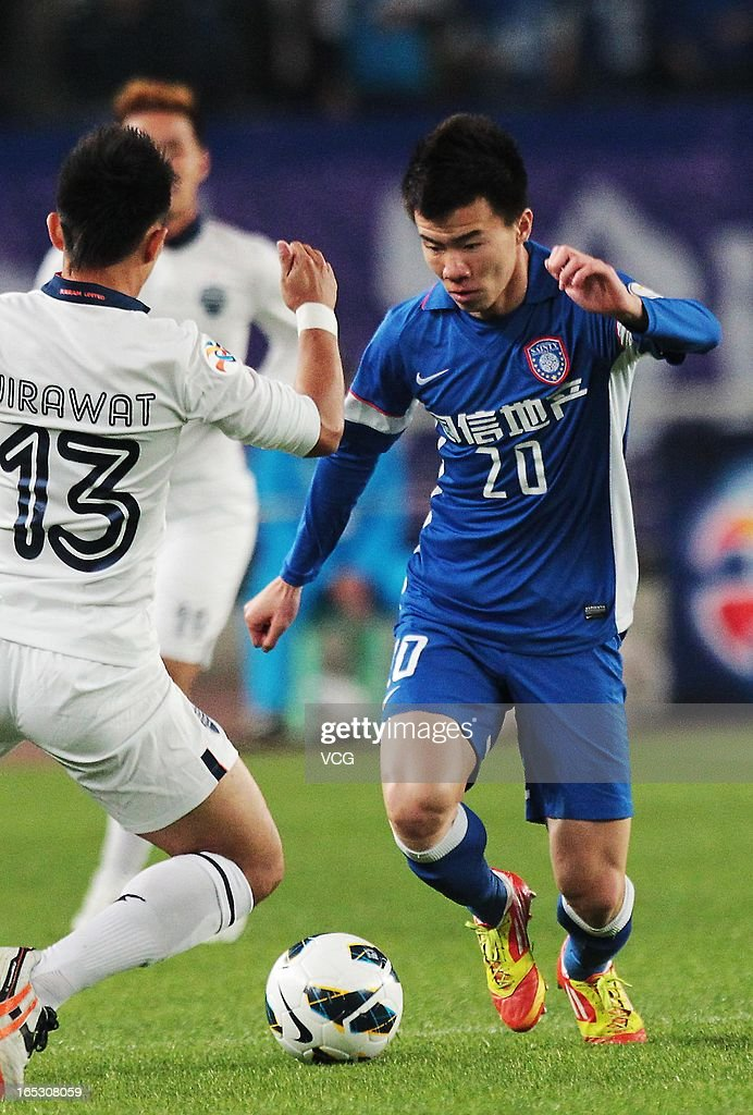 Sun Ke #20 of Jiangsu Sainty drives the ball past Jirawat Makarom #13 of Buriram United battle for the ball during the AFC Champions League match between Jiangsu Sainty and Buriram United at Nanjing Olympic Sports Center Stadium on April 2, 2013 in Nanjing, China.