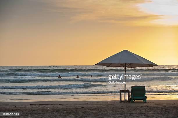 Sun lounger under umbrella on Legian Beach at sunset, Kuta, Bali, Indonesia